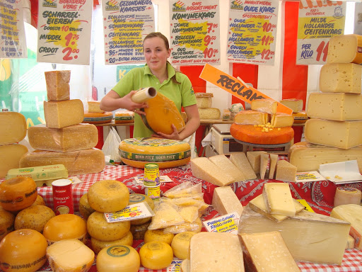 buy food at the local market, like these cheese in Amsterdam, to save money when traveling