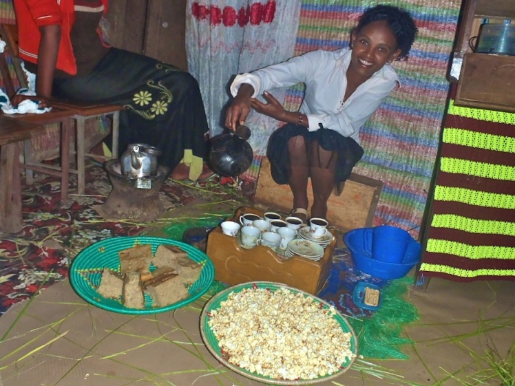 Ayantu performs a coffee ceremony at Faasika (Easter). She's pouring coffee from a jebena. The small charcoal stove for roasting coffee beans and boiling water is on the left.