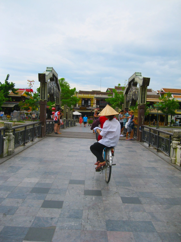 A bicyclist and passenger travel over the Japanese Bridge, the symbol of Hoi An. Photo by Charish Badzinski.