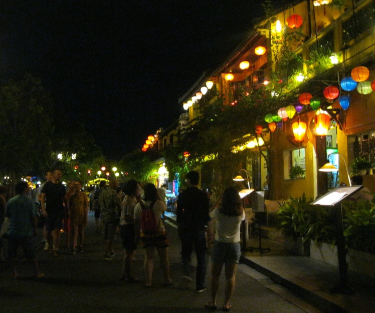 Tourists stroll through the old town section of Hoi An at night. Photo by Charish Badzinski.