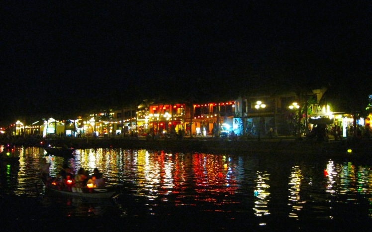 The city of Hoi An is reflected on the canal, by night. Photo by Charish Badzinski.