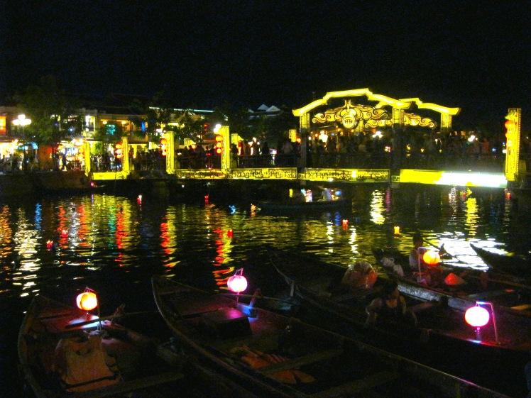 The Japanese bridge glows at night, as passenger boats wait for tourists. Photo by Charish Badzinski.
